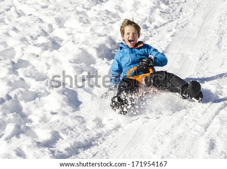 Cute young boy laughing as he is sledging downhill in the snow - stock photo