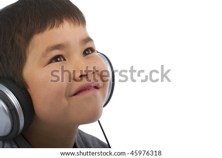 Cute young boy listening to music and smiling - stock photo
