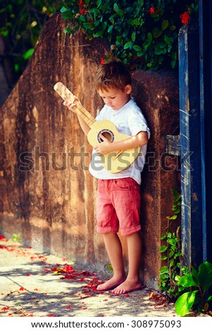 cute young boy playing guitar near the summer old fence - stock photo