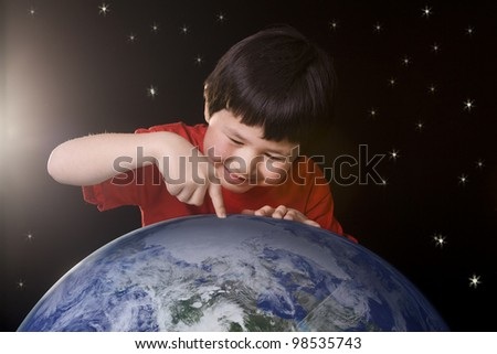 Cute young boy pointing to a spot on planet earth with space background and stars. Elements of this image furnished by NASA. - stock photo