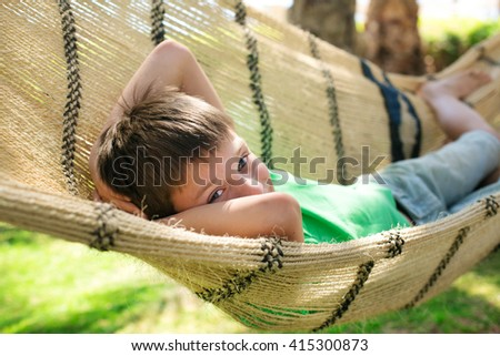 cute young boy resting in a hammock - stock photo