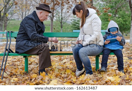 Cute young boy sitting on a park bench holding a tablet computer while his mother and grandfather play chess alongside him - stock photo