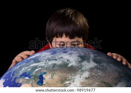 Cute young boy taking a close up look at a spot on planet earth with space background. Elements of this image furnished by NASA. - stock photo