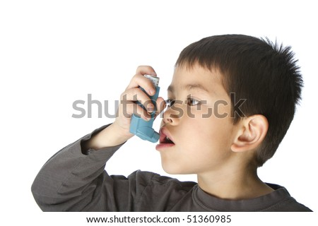 Cute young boy using his asthma inhaler isolated on white background - stock photo