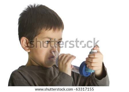 Cute young boy using his asthma inhaler with and aero chamber isolated on white background - stock photo