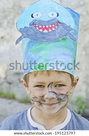 Cute young boy wearing a shark hat with his face painted - stock photo