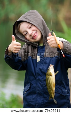 Cute young boy with great smile holding carp and show a thumb up - stock photo