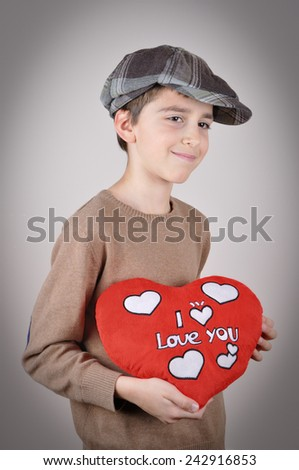 Cute young boy with newsboy cap holding a plush red heart with I love you message on Valentines day - stock photo