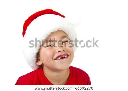 Cute young boy with two front teeth missing wearing a Christmas Santa hat isolated on white background - stock photo