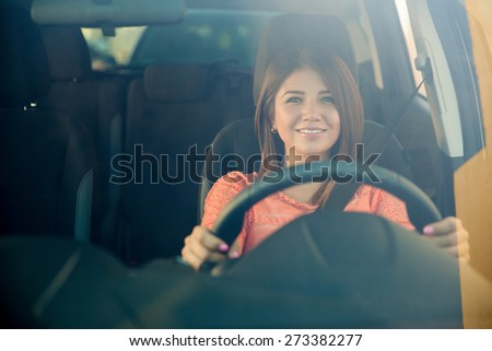 Cute young brunette enjoying a car ride and smiling, shot through the windshield - stock photo
