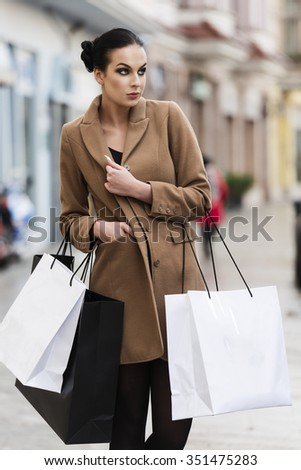 cute young brunette , in coat going for shop in winter time, she is carrying some shopping bag.  - stock photo