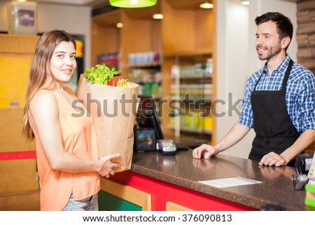 Cute young brunette ready to pay for her groceries at a checkout counter in a store - stock photo