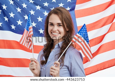 Cute young brunette woman celebrating National Independence Day on 4th of July in United States of America. Attractive model with toothy smile and flag on the background - stock photo