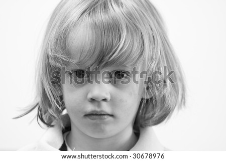 Cute young caucasian boy with blond hair looking serious - stock photo