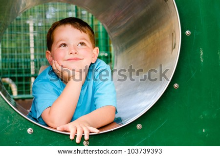 Cute young child boy or kid playing in tunnel on playground. - stock photo
