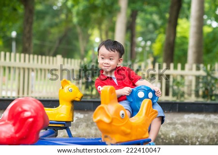 Cute young child boy or kid playing on playground. Cheerful asian boy  - stock photo