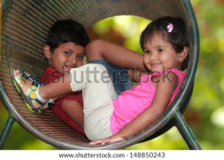 Cute young children ( boy & girl ) playing in tunnel on playground. The photo shows summer time playground with female kid smiling in a tube while the boy in the background looking on - stock photo