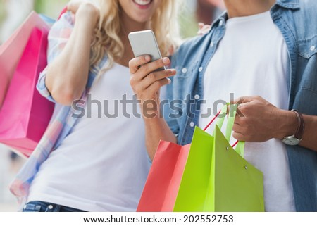 Cute young couple on shopping trip looking at smartphone on a sunny day in the city - stock photo