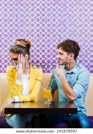 Cute young couple sitting at the table - stock photo