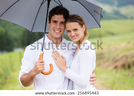 cute young couple under a umbrella - stock photo