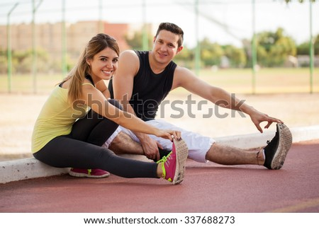 Cute young couple warming up and stretching together before working out outdoors - stock photo