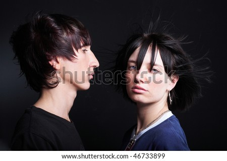 Cute young couple with fashion haircut, on black - stock photo
