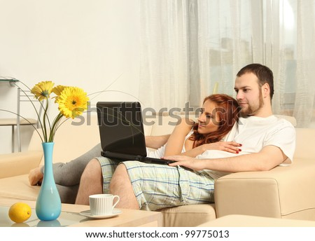 cute young couple with laptop - stock photo