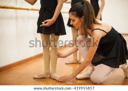 Cute young dance teacher helping her students with their posture during dance class - stock photo