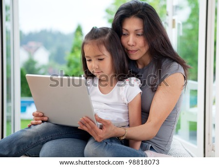 Cute young daughter together with mother using a laptop in a house interior - stock photo