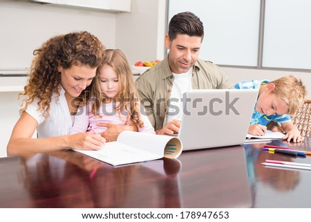 Cute young family at the table at home in kitchen - stock photo