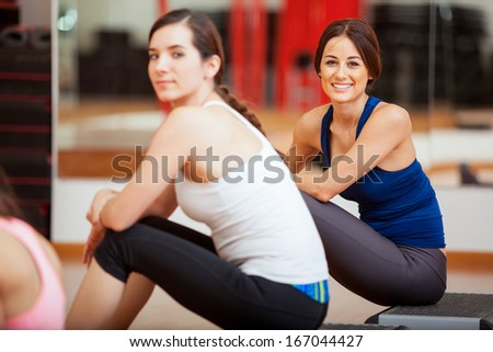 Cute young female friends taking a break from a class at a gym - stock photo