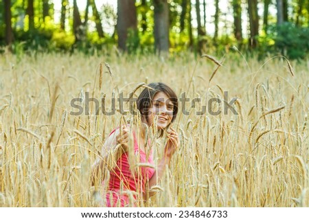 Cute young female stands in crop field with arms outstretched - stock photo