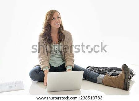 Cute young female student in sweater sitting with a backpack in studio - using a laptop computer - stock photo