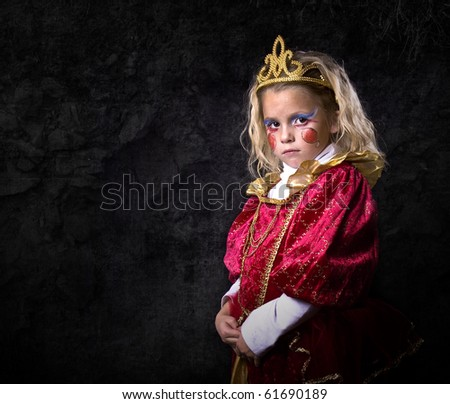 Cute young girl dressed up in a princess costume on a black background. - stock photo