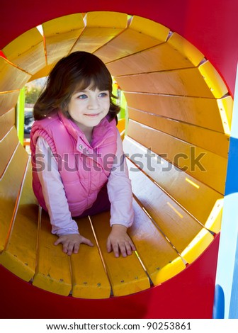 Cute young girl enjoys playing in tunnel in a children's playground - stock photo