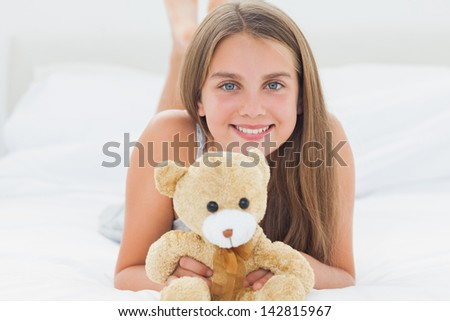 Cute young girl holding a teddy bear while she is lying on her bed - stock photo