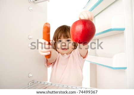 Cute young girl holding hot dog sausage and ripe red apple in refrigerator; healthy eating choices concept. - stock photo