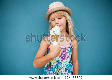 Cute young girl holding vanilla ice cream cone outside against blue wall background - stock photo