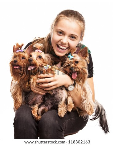 Cute young girl holding Yorkshire terrier dogs on her lap over white - stock photo