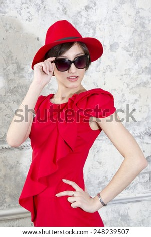 Cute young girl in a red hat and sunglasses - stock photo