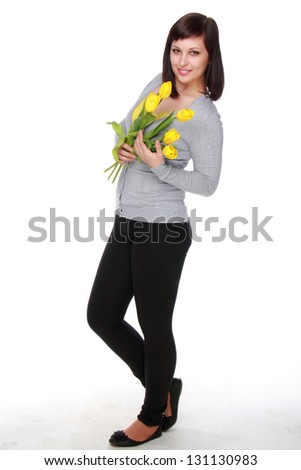 Cute young girl in casual wear with a beautiful bouquet of tulips on white background - stock photo
