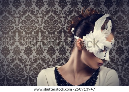 cute young girl in white dress with carnival mask looking down . feather on mask - stock photo
