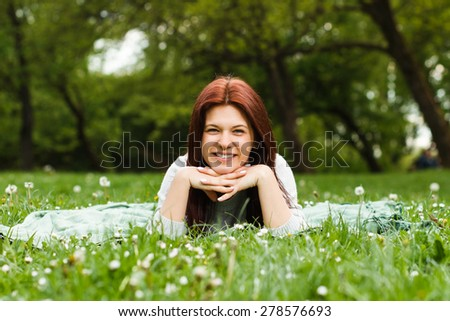 Cute young girl lying down in nature and looking at camera.Portrait of a young girl - stock photo