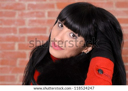 cute young girl posing against a brick wall - stock photo