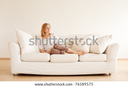 cute young girl relaxing on couch at home - stock photo