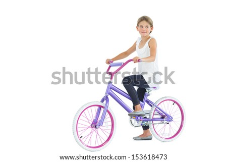Cute young girl riding bike while posing on white background - stock photo