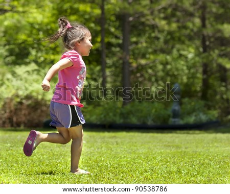 Cute young girl running in the yard - stock photo