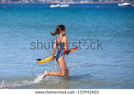 cute young girl runs with her surfboard in the sea water - stock photo