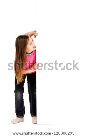 cute young girl standing next to empty blank board with copyspace - stock photo