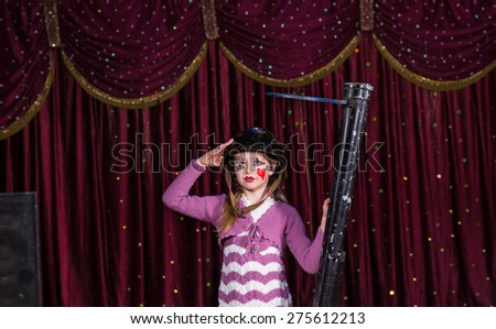 Cute young girl wearing a helmet and makeup holding a blunderbuss in her hand as she salutes the camera during a pantomime performance - stock photo